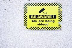 Ben bewuste 24 u-de veiligheidscamera van uurkabeltelevisie in verrichtings geel teken op witte muur Stock Foto's