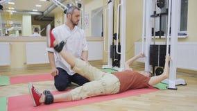 Ben för äldre kvinna för fysioterapeutportion som lyftande gör övningar i konditionrum Sund gymnastik Aktivt folk arkivfilmer