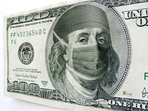 Ben Franklin Wearing Healthcare Mask on One Hundre. This photo illustration of Ben Franklin wearing a health care mask and bonnet on a one hundred dollar bill