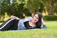Ben glimlachdame ontspannen op het gras stock foto