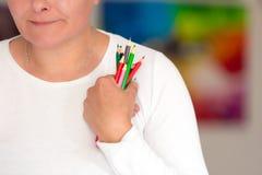 Ben I creatief? - holdingskleurpotloden in de hand stock afbeelding