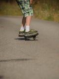 Ben i gymnastikskor på en skateboard Royaltyfri Bild