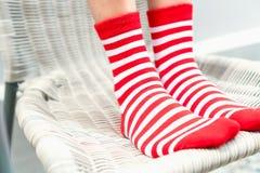 Ben i röda färger för sockor växlar, den vita sidoställningen på vit stol Arkivfoto