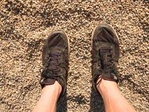 Ben i svart sport skor att gå på sandig jordning Ben för hårig hud för man i svarta skor Arkivfoton