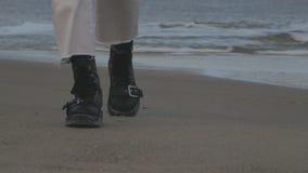 Ben i svarta skor för läder går på sanden nära havet stock video