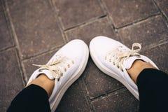 Ben i vita gymnastikskor med guld snör åt avkoppling ben för bakgrundspåsebegrepp som shoppar den vita kvinnan avkoppling för pil royaltyfri bild