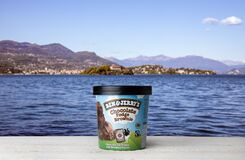 Ben Jerry`s Chocolate Fudge Brownie Ice Cream on white wooden table against blue water and mountains background