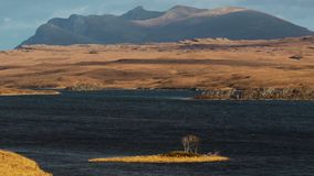 Ben Loyal in Nord-Schottland, Sutherland, wenn die Wolke über Spitzen treibt, mit tiefem blauem Loch im Vordergrund stock video footage