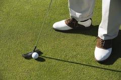 Ben med golfklubben och bollen på gräs Arkivfoto