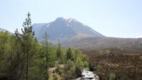 Ben Nevis Scotland UK snow topped mountain in summer with mountain stream in foreground, Lochaber Scottish Highlands stock footage
