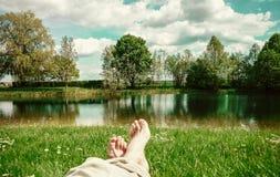 Ben och fot som kopplar av i det fridfulla sötvattendammet Royaltyfri Fotografi