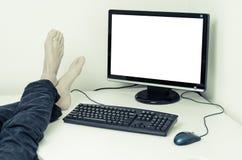 Ben och fot utan skor på skrivbordet med den vita skärmen Arkivbild