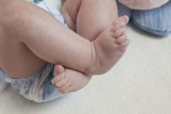 Ben och foten av behandla som ett barn med den blåa blöjan arkivfoton