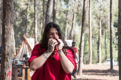 The bard - participant of the reconstruction `Viking Village` plays the harmonica in the camp in the forest near Ben Shemen in Isr Royalty Free Stock Image