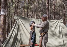 The participant of the reconstruction `Viking Village` Helps the visitor to wear armor in the camp in the forest near Ben Shemen i. Ben Shemen, Israel, November Royalty Free Stock Photo