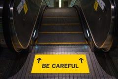 Ben zorgvuldige tekst op geel etiket bij roltrap Stock Foto's