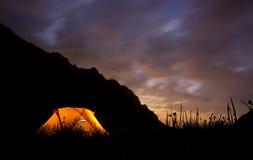 Benadrukte zonsondergang in bergen met tent Stock Afbeeldingen