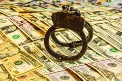 Benamingendollars van diverse geplaatste nominale waarde en handcuffs Stock Fotografie