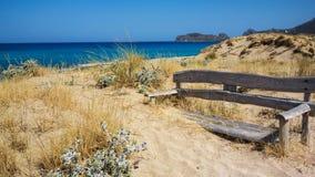 Bench на береге моря, покрытом с песком Стоковое Фото