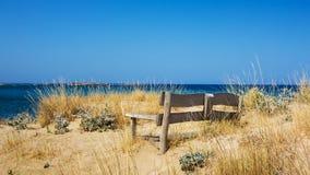 Bench на береге моря, покрытом с песком Стоковое Изображение RF
