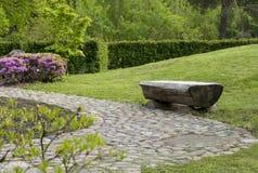 Bench от ствола дерева на лужайке, Буше с розовыми цветками, g Стоковые Фото