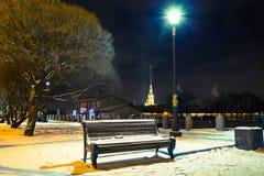 Bench, снег и уличный свет покрытые дорожкой на ноче Городской пейзаж зимы в Санкт-Петербурге, России Стоковые Изображения