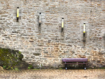 Bench. Abandoned bench under the walls of a big fortification royalty free stock images