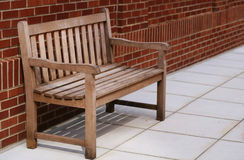Bench. Solitary bench against a brick wall Stock Image