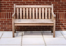 Bench. A solitary bench against a brick wall Royalty Free Stock Images