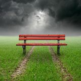 Bench. On green field relating to clouds Royalty Free Stock Photo