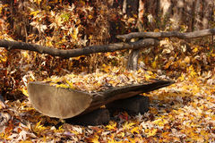 Bench. Simple wooden bench in the woods covered with foliage Royalty Free Stock Images