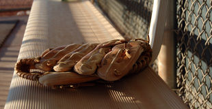 On The Bench. The soft glow of sunset falls on a baseball glove left on the bench after the game stock photo