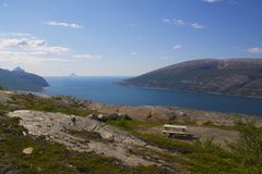 Bench above fjord. Bench for tourists high above a picturesque fjord near polar circle Royalty Free Stock Images