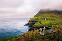 Bench above Gasadalur village with views over Atlantic Ocean on Faroe Islands