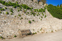 Bench against stone wall Royalty Free Stock Photography