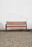 Bench against white wall on cobblestone street Stock Images