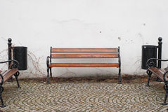 Bench against white wall on cobblestone street Royalty Free Stock Image