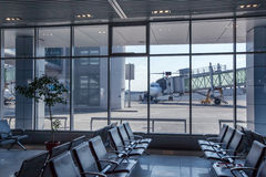 Bench in airport terminal and parked airplane Royalty Free Stock Images