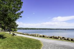 Bench along sidewalk on the shoreline of Canandaigua Lake. Sunny day and calm water on the lake. Rocks on the shoreline. Boats on the lake royalty free stock photo