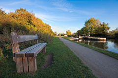 Bench alongside a canal towpath in autumn stock photo