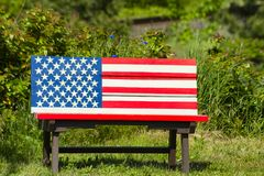 Patriotic Painted Bench in a park. A bench with the American Flag Painted on it invites one to sit royalty free stock images
