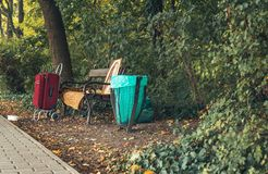 Bench in autumn park with sutitcase and homeless stuffs.  Royalty Free Stock Photos