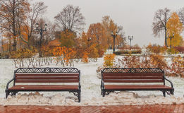 Bench in autumn park under snow. Horizontal photo, photo took in Tsaritsyno park,  Moscow, Russian, photo is usable on picture post card, calendar, gardening Royalty Free Stock Photo