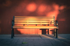A wooden bench before red wall. A classic wooden bench before red wall Stock Photo