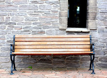 Bench on the background of a stone wall Stock Photo