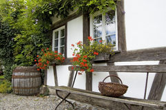 Bench And Basket. A wooden bench in front of antique half-timbered European private house, partially overgrown by a climbing plant Stock Image