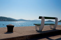 Bench in bay. A bench overlooking a bay in the mediterranean Stock Photo