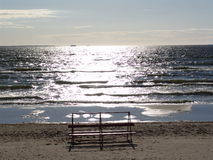 Bench on the beach. And sunny way on the sea Stock Image