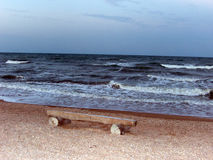 Bench on The beach. Bench on the seafront in the open arms of the sea waves Royalty Free Stock Image