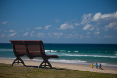 Bench by the beach with surfers in background Royalty Free Stock Images
